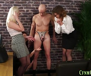 Classy dominas toying sissys ass and jerking his dick whilst clothed
